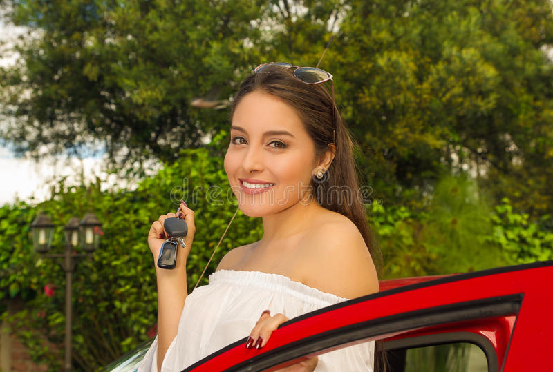 Portrait of a beautiful young woman in red car holding keys and smiling.  stock photography