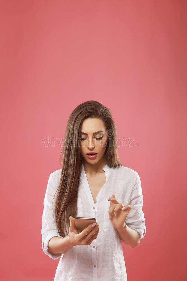 Portrait of beautiful shocked young woman posing  over pink wall background using mobile phone. royalty free stock photography