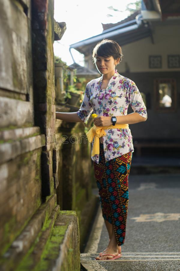 A portrait of a beautiful short-haired woman with a flower on his ear. She is wearing a bali dress with floral motifs, posing with stock photography