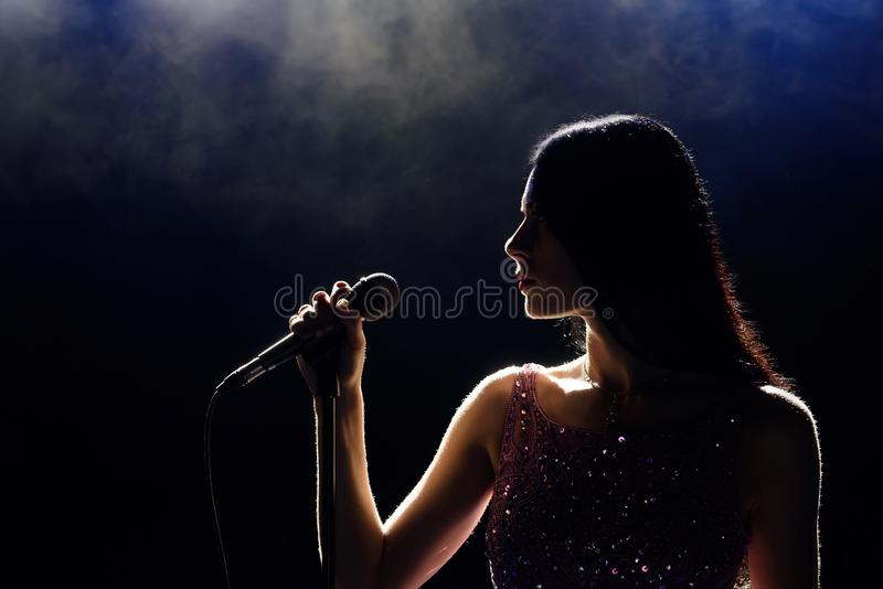 Portrait of beautiful singing woman on dark background royalty free stock photo