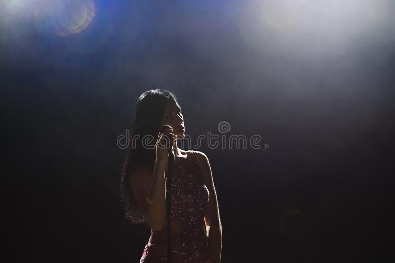 Portrait of beautiful singing woman on dark background. royalty free stock photography