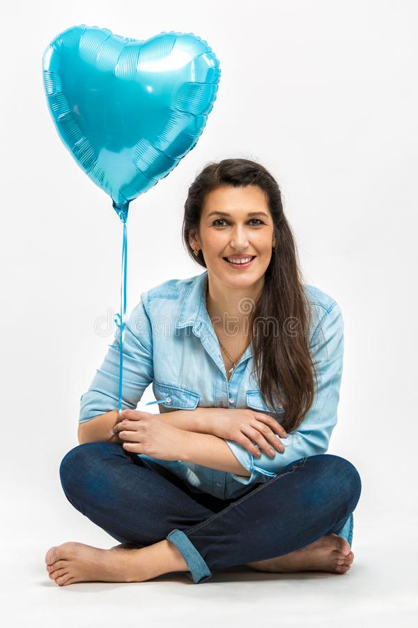 Portrait of a beautiful smiling adult woman with a blue balloon in the shape of a heart stock photo