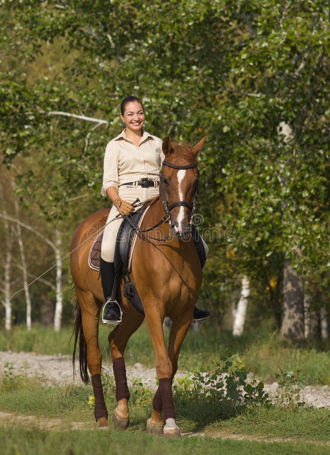Portrait of beautiful smiling brunette horsewoman royalty free stock photography