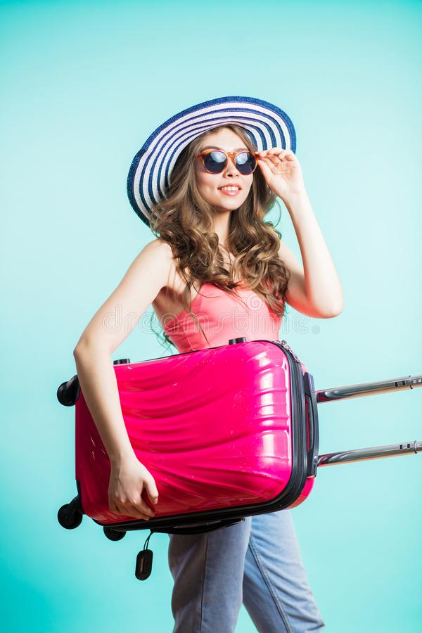 Portrait of beautiful smiling brunette woman in pink top, jeans and with suitcase on hand on blue background royalty free stock images