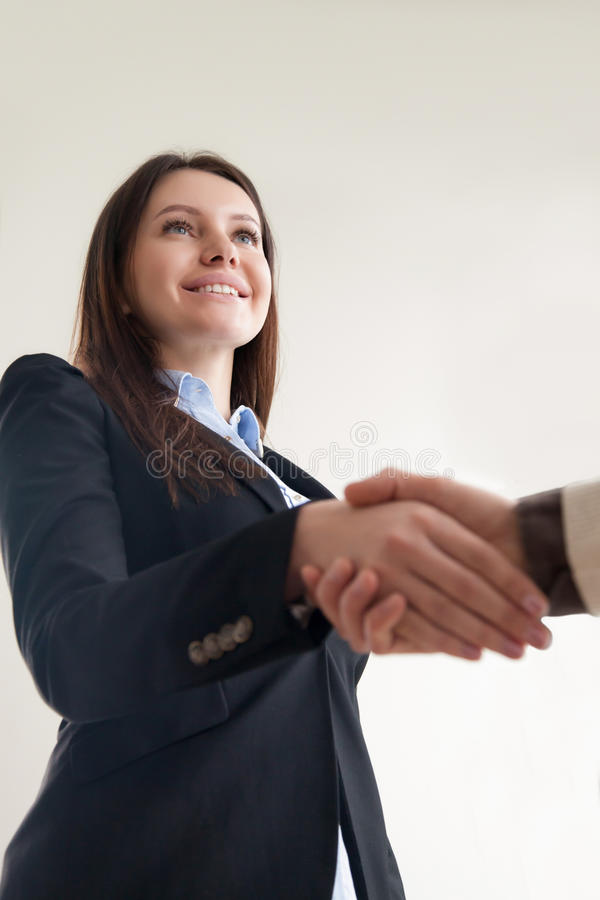 Portrait of beautiful smiling business lady shaking male hand, v royalty free stock image