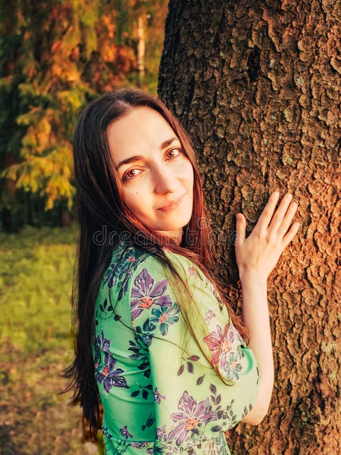Portrait beautiful smiling caucasian brunette girl with long hair in the forest at sunset leaned against a tree. Unity royalty free stock photography