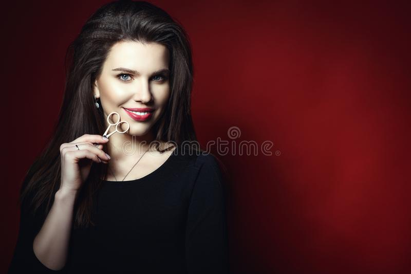 Portrait of beautiful smiling eyebrow master holding eyebrow scissors at her face royalty free stock photo