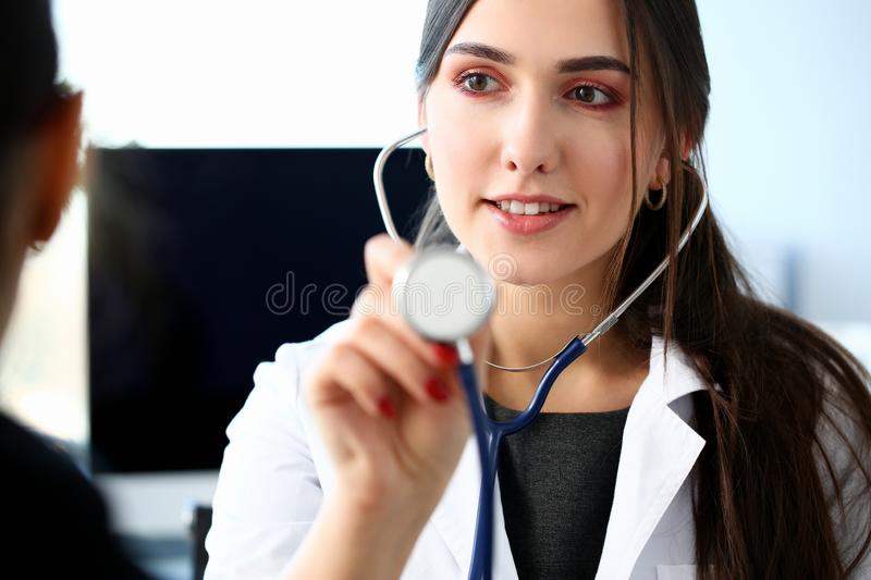 Portrait beautiful smiling female doctor hold. In arm stethoscope head going to listen patient. Tool shop or store physical disease prevention er consultant 911 stock photo
