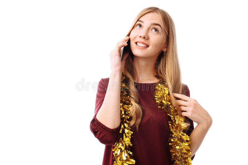Portrait of a beautiful smiling girl, dressed in a red dress, talking on a mobile phone, standing and looking to the side, isolate stock photo