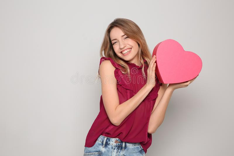 Portrait of beautiful smiling girl with heart shaped gift box on light background. stock photography