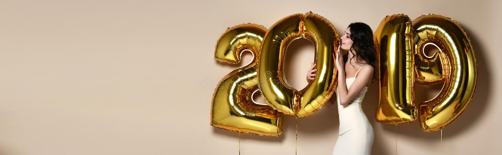 Portrait Of Beautiful Smiling Girl In Shiny Golden Dress Throwing Confetti, Having Fun With Gold 2018 Balloons On Background. stock photo