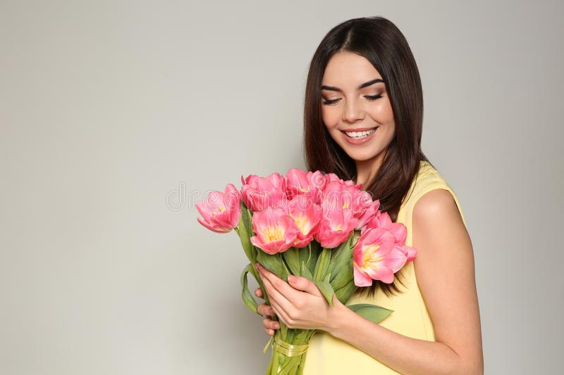 Portrait of beautiful smiling girl with spring tulips on light background, space for text. royalty free stock photography