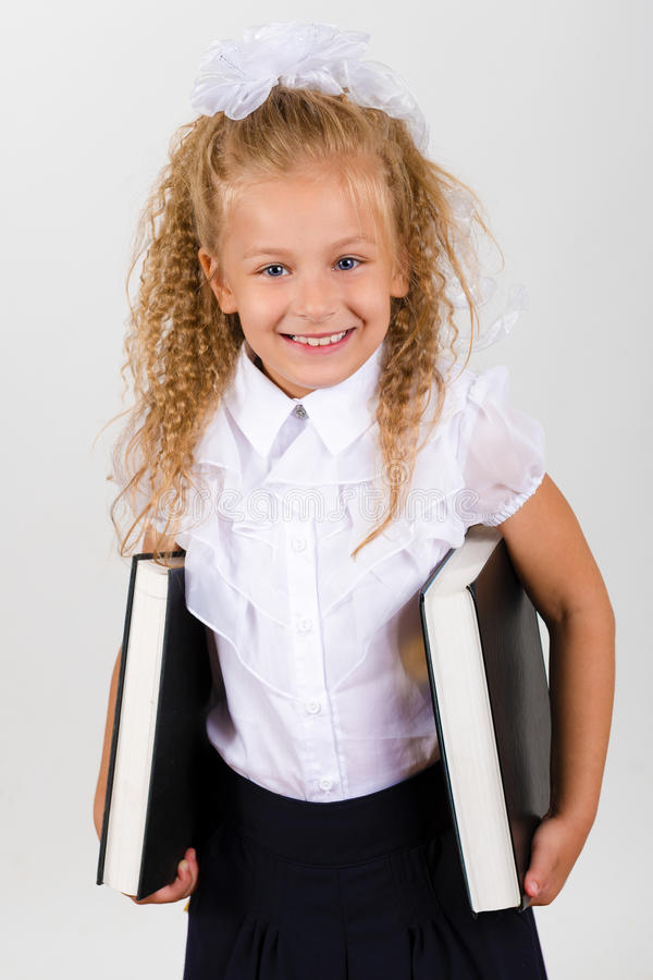 Portrait of beautiful smiling little girl in a school uniform royalty free stock photos