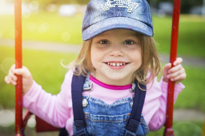 Portrait of a beautiful smiling little girl in a summer park on a swing. A happy cute baby is riding on a swing royalty free stock images