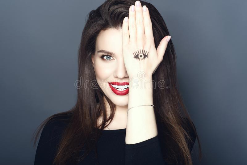 Portrait of beautiful smiling make up artist hiding her eye behind the hand with the eye drawn on it stock image