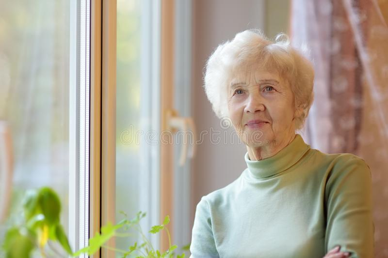 Portrait of beautiful smiling senior woman with curly white hair. Elderly lady is standing by window at home royalty free stock photography