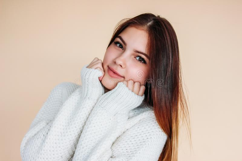 Portrait of beautiful smiling teenager girl with clean skin and dark long hair in cozy white sweater on beige background royalty free stock photo