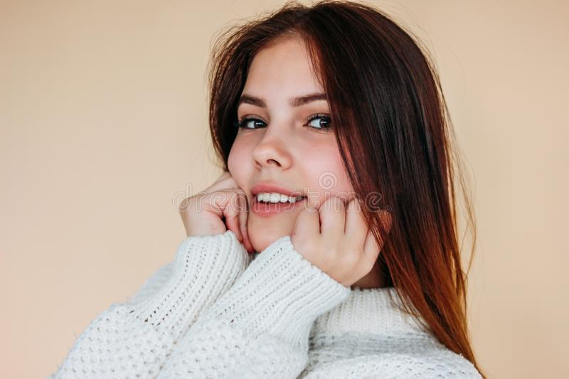 Portrait of beautiful smiling teenager girl with clean skin and dark long hair in cozy white sweater on beige background royalty free stock photography