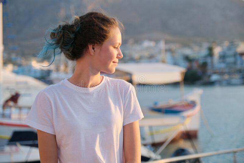 Portrait of beautiful smiling teenager girl in profile looking to the side stock photo