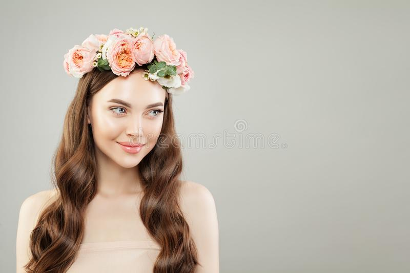 Portrait of beautiful smiling woman with clear skin, long shiny hair and flowers. Skincare and facial treatment concept stock photo