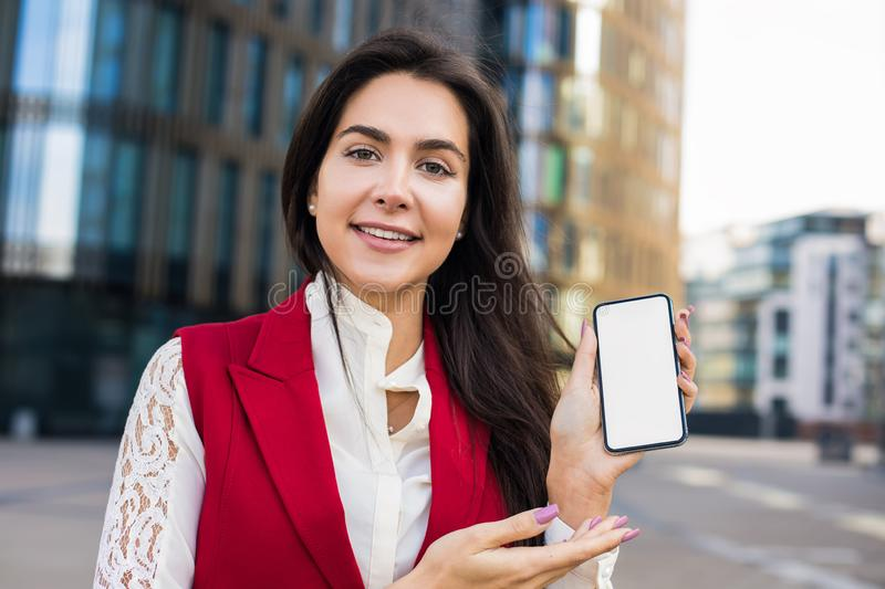 Portrait of a beautiful smiling woman professional business worker looking in camera and holding in hand mobile phone stock images