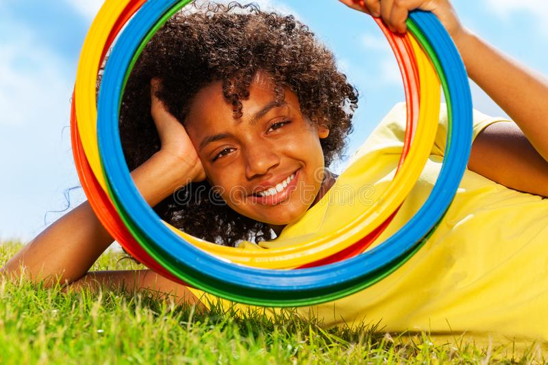 Portrait of girl look through color hoops on grass. Portrait of beautiful smiling young black mixed-race girl looking through color hoops rings laying on grass stock image