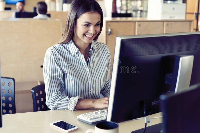 Portrait of beautiful smiling young brunette businesswoman sitting at bright modern work station and typing on computer stock image