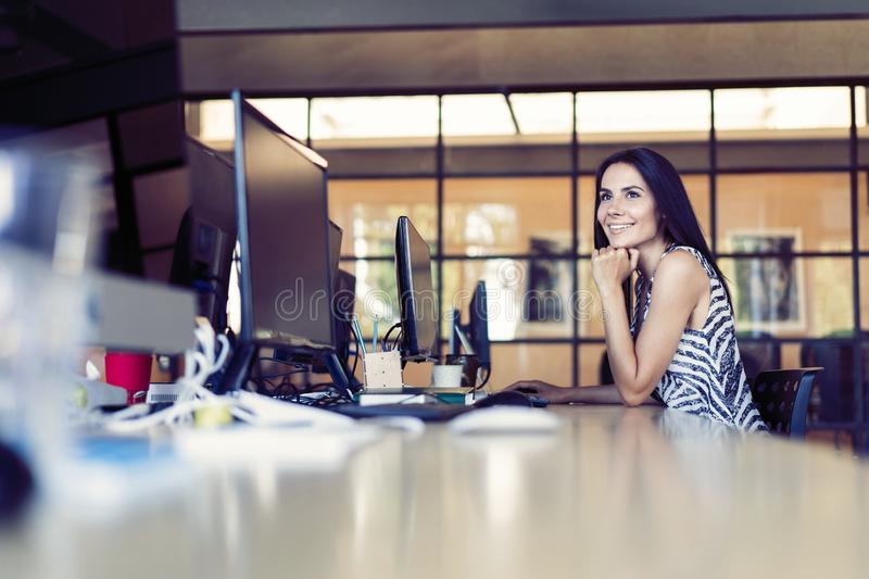 Portrait of beautiful smiling young brunette businesswoman sitting at bright modern work station and typing on computer royalty free stock images