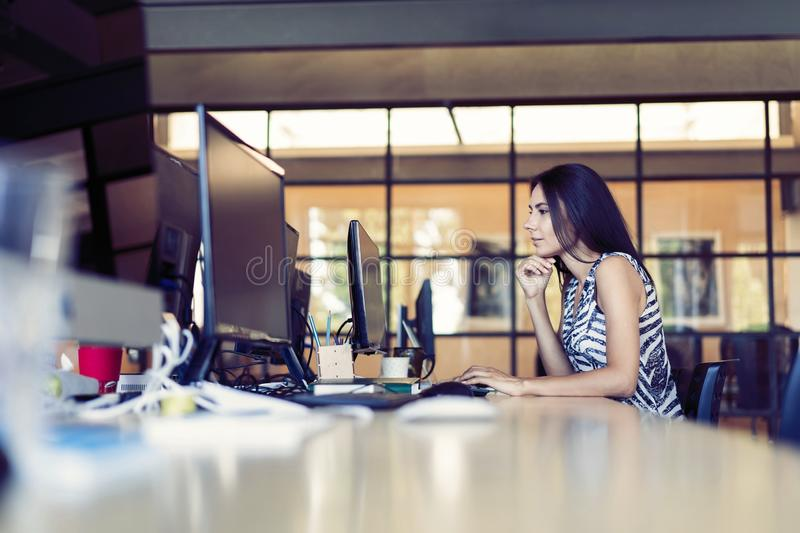Portrait of beautiful smiling young brunette businesswoman sitting at bright modern work station and typing on computer royalty free stock photos