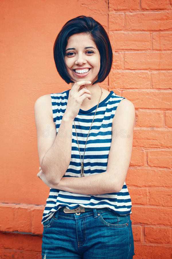 Portrait of beautiful smiling young hipster latin hispanic girl woman with short hair bob. In blue jeans, striped tshirt, leaning on red brick wall in city stock photos
