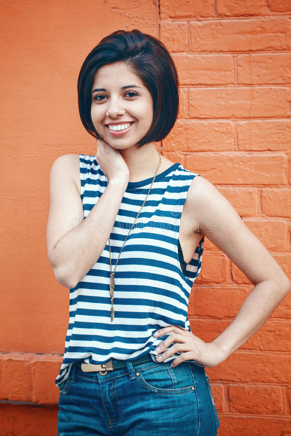 Portrait of beautiful smiling young hipster latin hispanic girl woman with short hair bob, in blue jeans, striped tshirt. Leaning on red brick wall in city royalty free stock photography