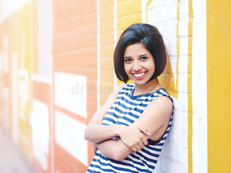 Portrait of beautiful smiling young hipster latin hispanic girl woman with short hair bob. In blue white striped tshirt, leaning on brick wall in city looking stock photos