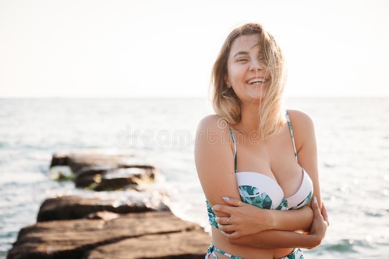 Portrait of beautiful smiling young woman in bikini on beach. Female model posing in swimsuit on sea shore. Summer holidays, royalty free stock images
