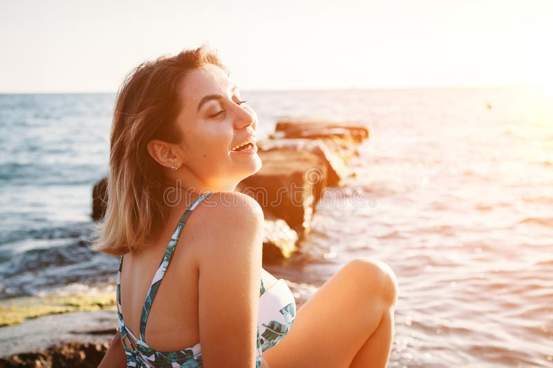 Portrait of beautiful smiling young woman in bikini on beach. Female model posing in swimsuit on the sea shore. Summer holidays, royalty free stock photography