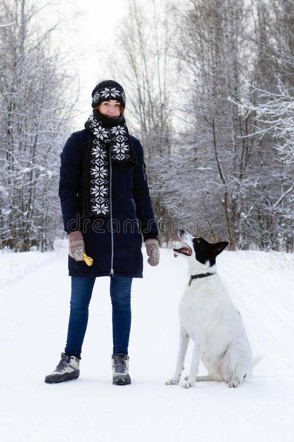 Portrait of beautiful smiling young woman with her black-white dog on a background of winter forest royalty free stock photos