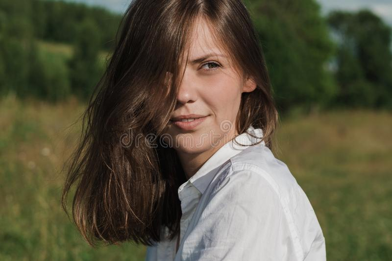 Portrait of a beautiful smiling young woman outdoors. Photo closeup royalty free stock photo