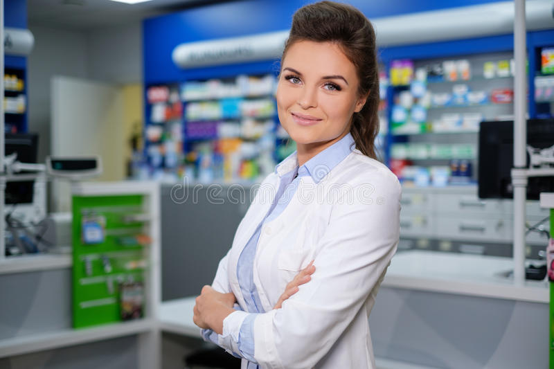 Portrait of beautiful smiling young woman pharmacist standing in pharmacy. royalty free stock photos