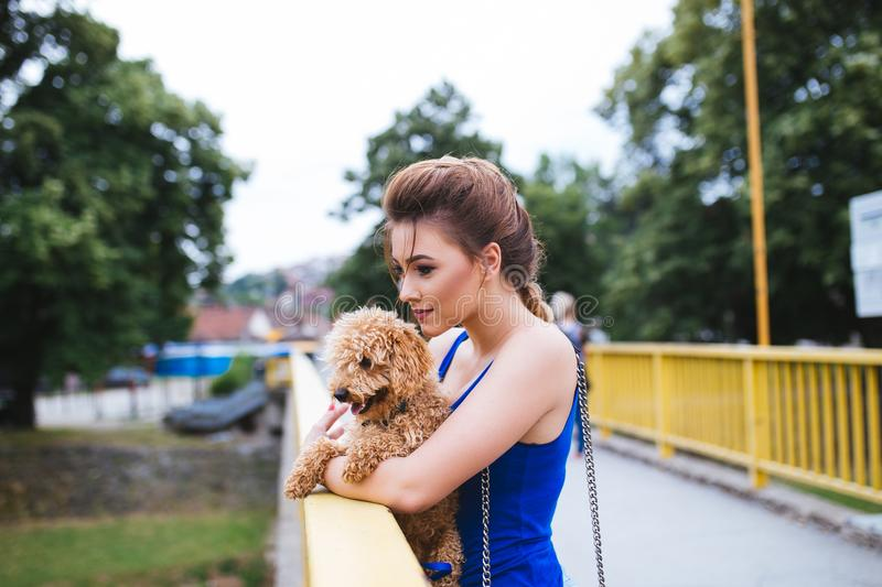 Teenager girl with red poodle. Portrait of beautiful smiling young woman standing on bridge with her little red poodle puppy royalty free stock photography