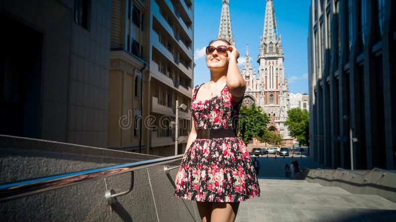 Portrait of beautiful smiling young woman in sunglasses posing against modern building and old catholic cathedral in stock images