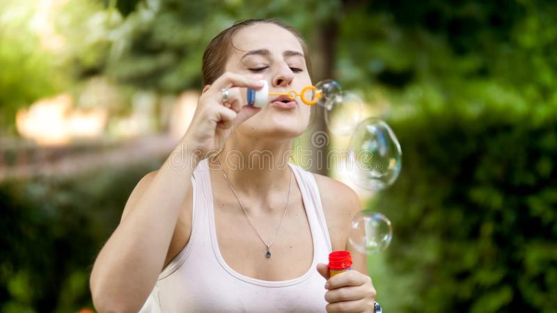 Closeup portrait of beautiful smiling young woman blowing soap bubbles in park at sunset royalty free stock images