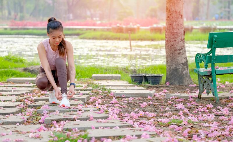 Portrait of beautiful sport girl is tiring shoelace on bricks and pink flower spread to the floor in the garden with morning light.  stock images