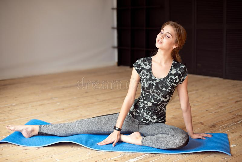 Portrait of a beautiful sports girl in sportswear resting after a fitness workout drinking water from a bottle sitting. On the floor in the gym stock photography