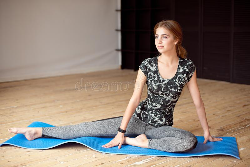 Portrait of a beautiful sports girl in sportswear resting after a fitness workout drinking water from a bottle sitting. On the floor in the gym royalty free stock photography