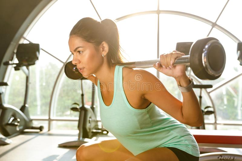Portrait of beautiful sportswoman in tracksuit doing sit-ups wit. H barbell while working out in gym royalty free stock photos