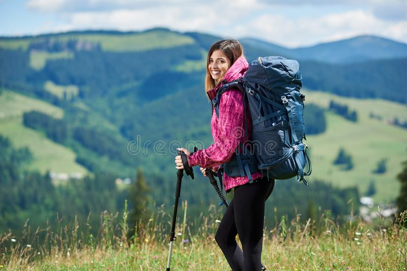 Sporty woman tourist with backpack and trekking sticks hiking in the mountains. Portrait of beautiful sporty woman hiker with blue backpack and trekking sticks royalty free stock photos