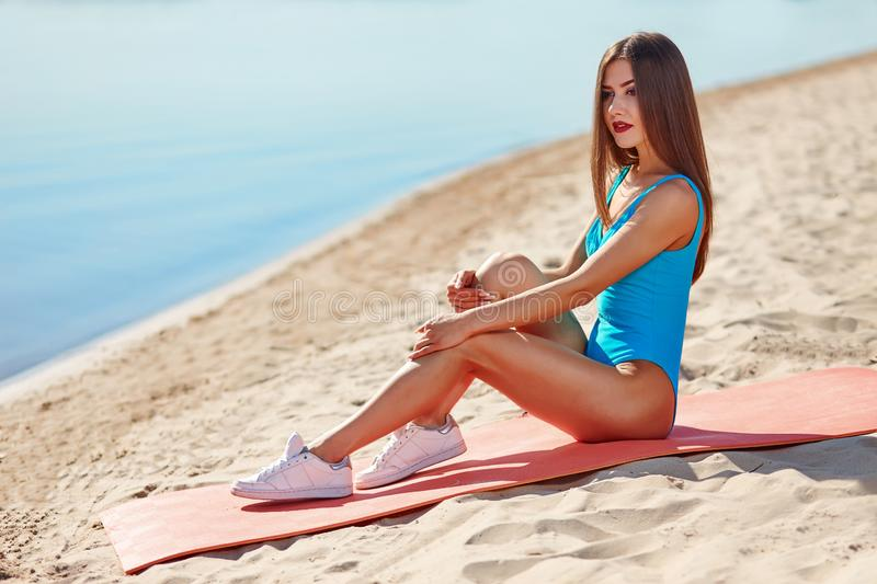 Portrait of beautiful sporty woman in swimwear doing workout fitness stretching exercises on the sand beach at early morning. royalty free stock photos
