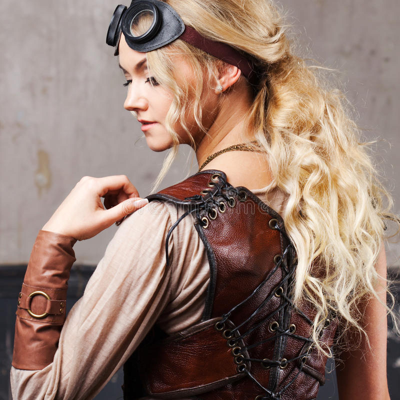 Portrait of a beautiful steampunk woman in Aviator glasses over grey background. Portrait of a beautiful steampunk woman over grunge background royalty free stock photo