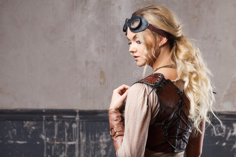 Portrait of a beautiful steampunk woman in Aviator glasses over grey background. Portrait of a beautiful steampunk woman over grunge background royalty free stock photography