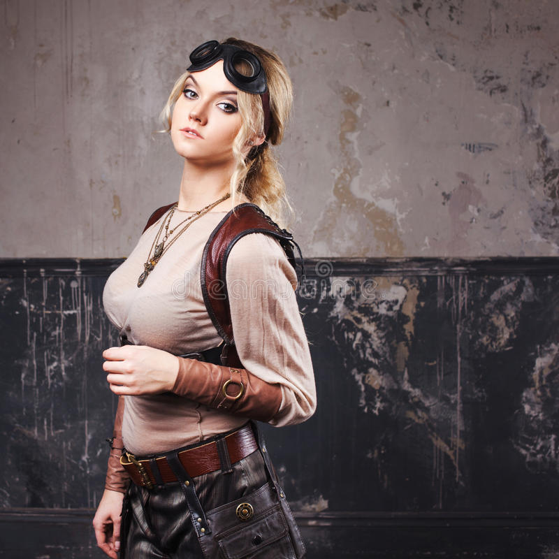 Portrait of a beautiful steampunk woman in Aviator glasses over grey background. Portrait of a beautiful steampunk woman over grunge background stock photos