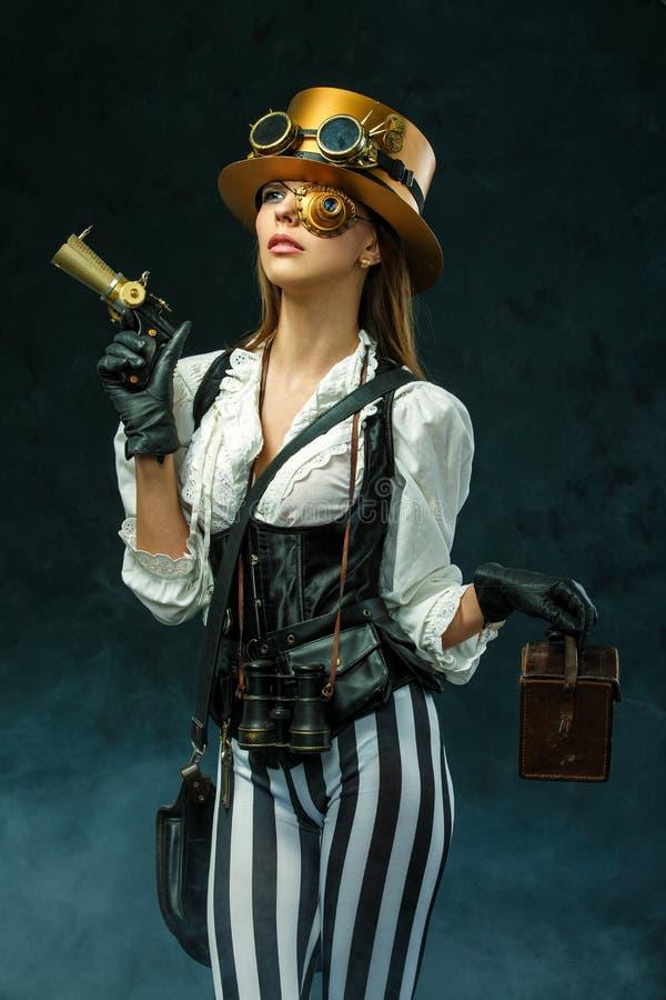 Portrait of a beautiful steampunk woman holding a gun stock photo